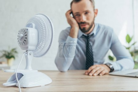 Photo for Selective focus of businessman in office with white electric fan - Royalty Free Image