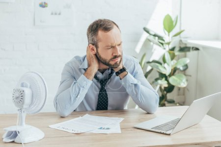 tired businessman sitting in office with electric fan, laptop and documents