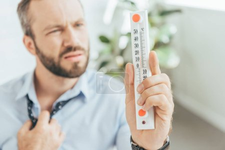 selective focus of businessman in hot office looking at thermometer
