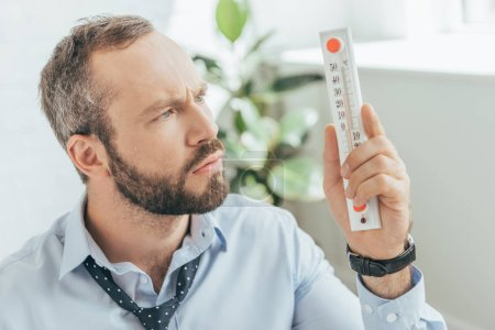 confused businessman in hot office looking at thermometer