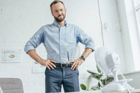 confused sweaty businessman looking at electric fan in office