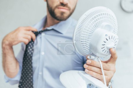 cropped view of businessman cooling himself with electric fan