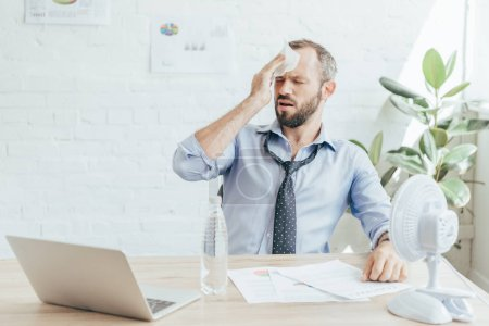 tired businessman with headache sitting at workplace with electric fan, bottle of water, paperwork and laptop