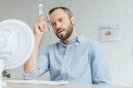 homme d'affaires lui-même avec une bouteille d'eau de refroidissement et de conditionnement d'air avec ventilateur électrique au bureau