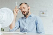businessman cooling himself with bottle of water and conditioning air with electric fan in office