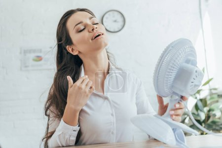 businesswoman conditioning herself with electric fan in office