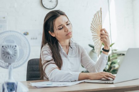 Photo for Exhausted businesswoman using laptop while conditioning air with electric fan and hand fan in office - Royalty Free Image