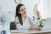"""Постер, картина, фотообои """"исчерпаны бизнесвумен, используя ноутбук при кондиционирования воздуха с электрическим вентилятором и веер в офисе"""""""