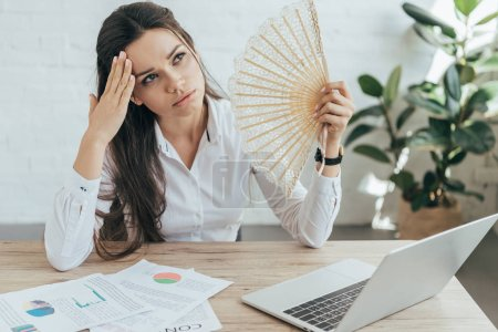 businesswoman in hot office with laptop and documents blowing herself with hand fan