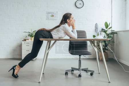 businesswoman conditioning air with electric fan at workplace in office
