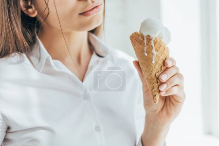 cropped view of woman holding melting ice cream in cone