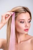 """Постер, картина, фотообои """"привлекательный молодой женщины, применяя Розовая клип волосы прядь изолированные на серый"""""""