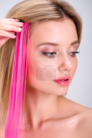 beautiful young woman applying pink clip-on hair strand isolated on grey