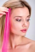 """Постер, картина, фотообои """"красивая молодая женщина, применяя Розовая клип волосы прядь изолированные на серый"""""""