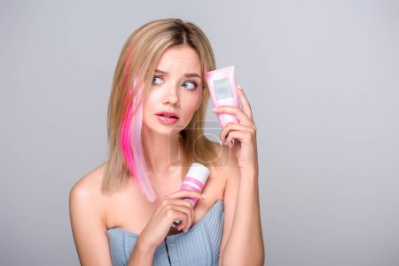 bewildered young woman with colored bob cut holding hair care supplies isolated on grey