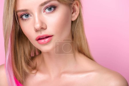 close-up portrait of beautiful young woman with colorful hair strands looking at camera isolated on pink