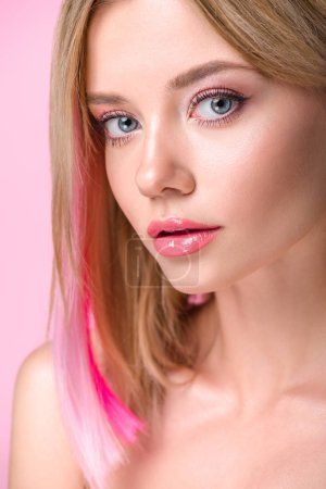close-up portrait of attractive young woman with colorful hair strands looking at camera isolated on pink