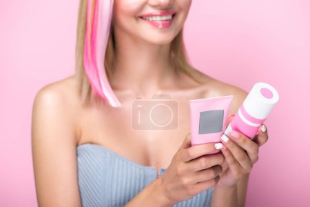 cropped shot of young woman with colorful hair strands holding hair treatments isolated on pink