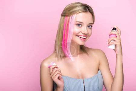 smiling young woman with colorful strands of hair and spray paint looking at camera isolated on pink