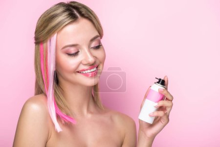 smiling young woman with colorful strands of hair and spray paint isolated on pink