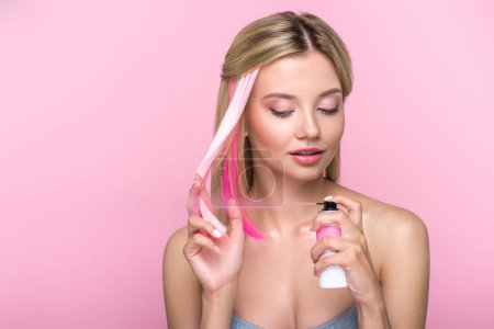 attractive young woman painting strand of hair with spray isolated on pink