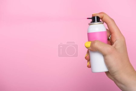 cropped shot of woman with yellow nails holding spray paint for hair isolated on pink