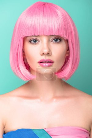 close-up portrait of young woman with pink bob cut and stylish makeup looking at camera isolated on turquoise