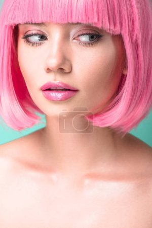 close-up portrait of young woman with pink bob cut looking at side isolated on turquoise