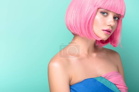attractive young woman with pink bob cut looking at camera isolated on turquoise