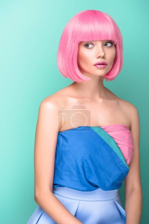 beautiful young woman with pink bob cut and dress looking away isolated on turquoise