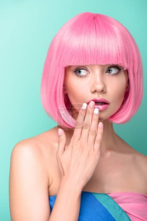shocked young woman with pink bob cut covering mouth with hand isolated on turquoise