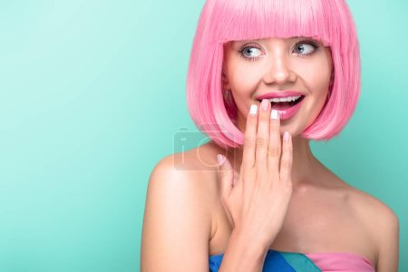 smiling young woman with pink bob cut covering mouth with hand isolated on turquoise