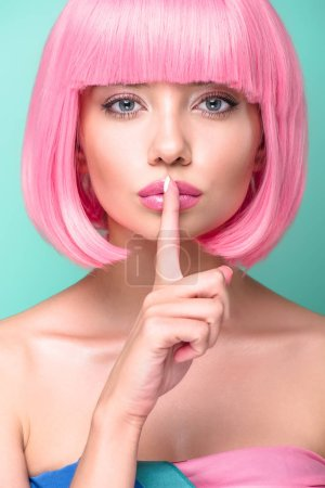 Photo for Close-up portrait of young woman with pink bob cut showing silence gesture and looking at camera isolated on turquoise - Royalty Free Image