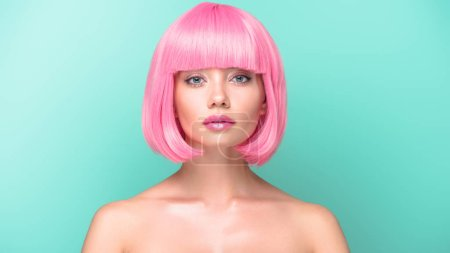 confident young woman with pink bob cut looking at camera isolated on turquoise