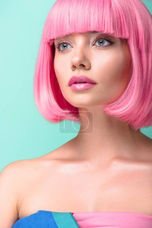 close-up portrait of young woman with pink bob cut looking away isolated on turquoise