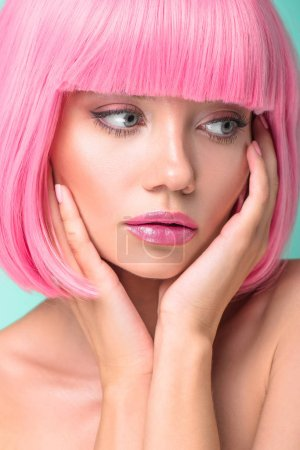 close-up portrait of thoughtful young woman with pink bob cut  isolated on turquoise
