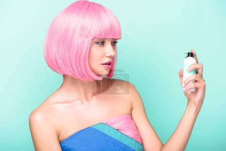beautiful young woman with pink bob cut holding coloring hair spray isolated on turquoise