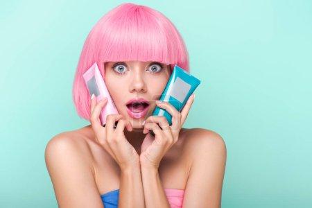 Photo pour Choqué jeune femme avec des tubes de coloration tonique des cheveux en regardant la caméra isolée sur turquoise - image libre de droit