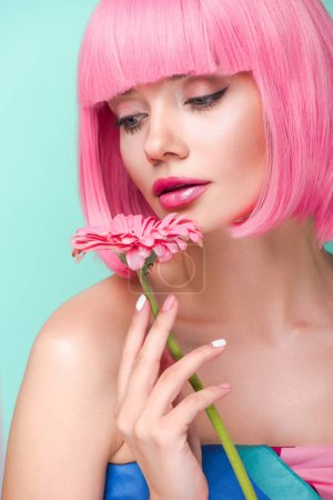beautiful young woman with pink bob cut holding flower isolated on turquoise