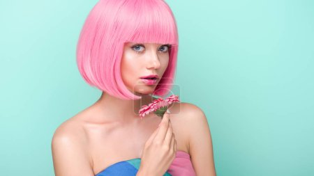attractive young woman with pink bob cut holding flower isolated on turquoise