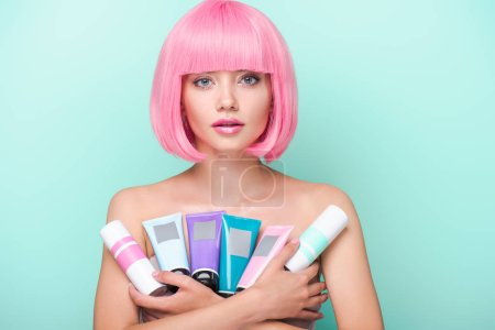 young woman with pink bob cut holding various tubes of coloring hair tonics looking at camera isolated on turquoise