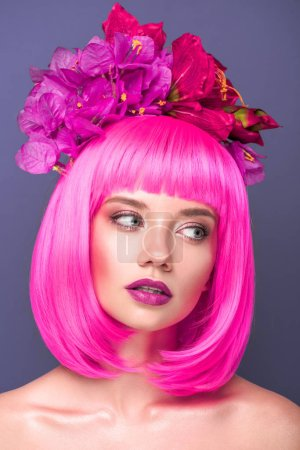 attractive young woman with pink bob cut and flowers in hair looking away isolated on violet