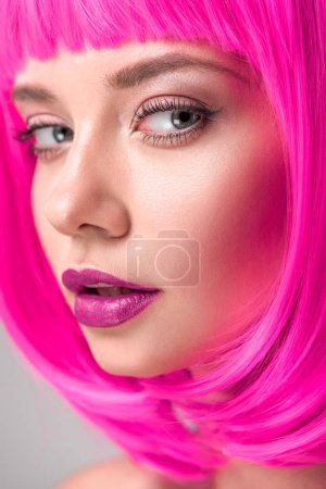 attractive young woman with pink bob cut looking at camera