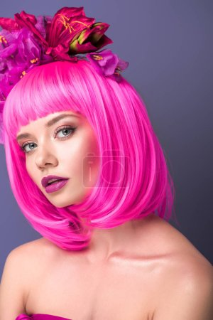 attractive young woman with pink bob cut and flowers in hair looking at camera isolated on violet