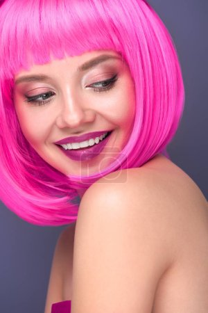 close-up portrait of smiling young woman with pink bob cut isolated on violet