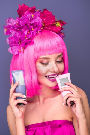 smiling young woman with pink bob cut and flowers in hair holding tubes of coloring hair tonics isolated on violet