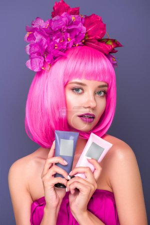 beautiful young woman with pink bob cut and flowers in hair holding tubes of coloring hair tonics isolated on violet