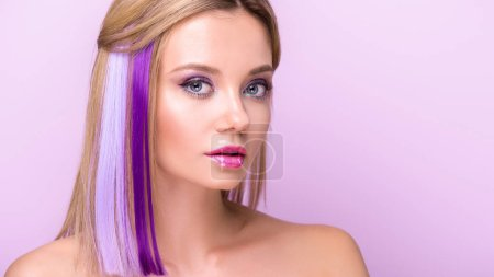 close-up portrait of beautiful young woman with stylish makeup and purple hair strands looking at camera isolated on purple