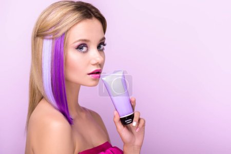 beautiful young woman with bobbed hair with purple strands and coloring hair tonic looking at camera isolated on purple