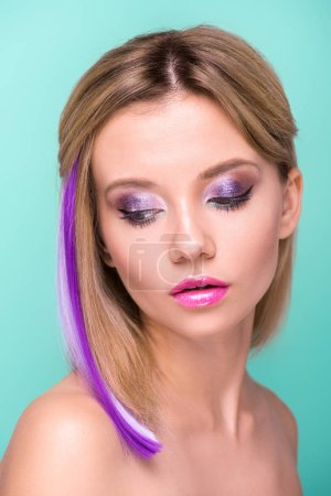 Photo for Close-up portrait of attractive young woman with stylish makeup and purple hair strand isolated on blue - Royalty Free Image